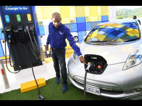 Richard Gordon, manager, Business Development, Jamaica Public Service Company charging an electric vehicle during the comissioning of the first Public Electric Vehicle Charging Station at Boots Service Station, Drax Hall, St. Ann on Friday,