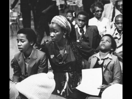 Rita Marley, widow of reggae superstar Bob Marley, and her two sons, Ziggy (left), and Stephen, attend Marley's funeral in Kingston on May 21, 1981.