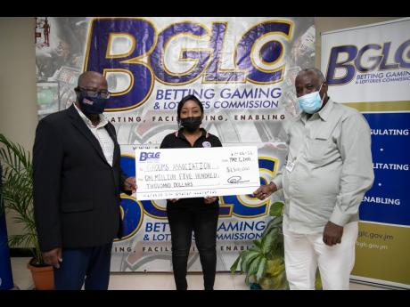 From left: Betting, Gaming and Lotteries Commission (BGLC) Executive Director Vitus Evans, Jamaica Racing Commission official Kavel Buckley, and Grooms Association President Fabian White at a symbolic handover of a $1.5-million cheque by the BGLC to the Gr