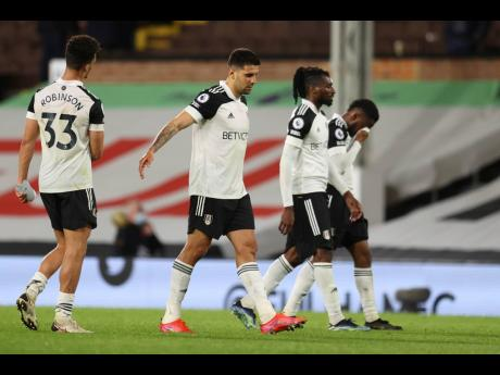 Fulham's Aleksandar Mitrovic (centre) walks off the field in despair with his teammates after being relegated from the English Premier League yesterday. It happened in their 2-0 to Burnley at Craven Cottage in London, England, yesterday.