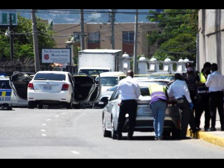 Policemen huddle at the intersection of Hope, Waterloo, and Trafalgar - the scene of a firefight between law enforcers and the alleged killers of businessman Robert Fletcher on Monday. Fletcher was slain at his Travellers Rest Sports Bar minutes before his