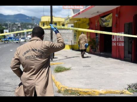 A forensic investigator enters the crime scene where Robert Fletcher was slain at his sports bar on Monday. Cash and his licensed firearm were stolen.