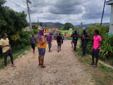 Police officers keep a close watch as residents of All-Side in Trelawny vent their anger over the alleged circumstances under which Kimorlay Forbes was killed.