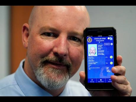 Ryan Williams, with the Utah Drivers License Division, displays his cell phone with the pilot version of the state's mobile ID on Wednesday, May 5, 2021, in West Valley City, Utah.