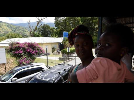 A young mother stands with her daughter in-hand outside the closed gates of the Mavis Bank Health Centre in St Andrew.