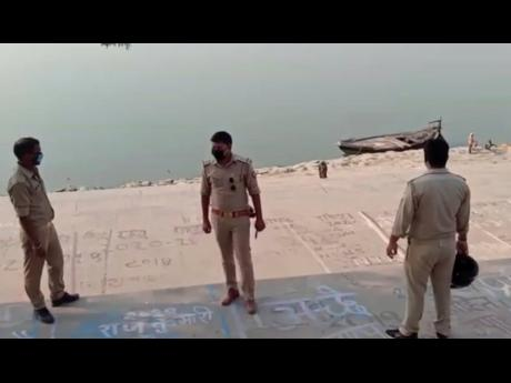 This frame grab from video provided by KK Productions shows police officials standing guard at the banks of the river where several bodies were found lying in Ghazipur district, Uttar Pradesh state, India, on Tuesday.
