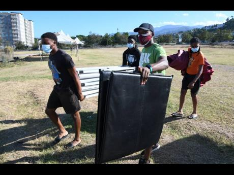 Team members of Herbert Morrison Technical High pack up equipment and prepare to leave the Stadium East field to participate in Day One action of the ISSA/GraceKenneday Boys and Girls' Championships at the National Stadium in Kingston on Tuesday.