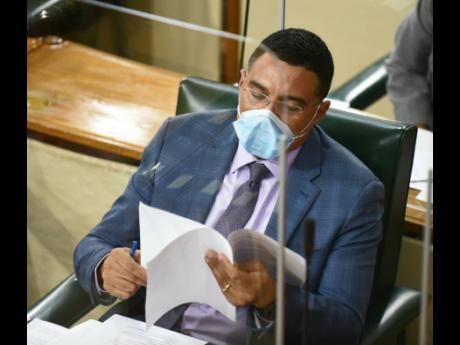 Prime Minister Andrew Holness pores over a document during Tuesday's sitting of the House.