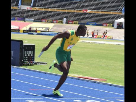St Jago High School's Kimarlie Stewart anchors his team to victory in their semifinal heat in the Class One Boys 4x100m relay event at the ISSA/GraceKennedy Boys and Girls Championships at the National Stadium on Wednesday.