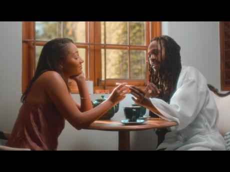 Female lead and model Natasha St Cyr (left) and Jesse Royal share tea and a joint in a scene from the video.