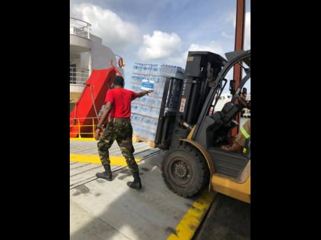 Cases of water are loaded onto the vessel headed for Saint Vincent with relief supplies.