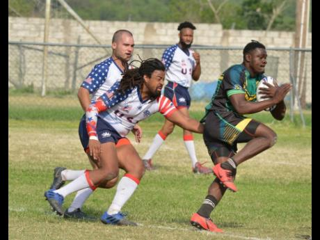 Roland Grey (right) of the Jamaica Reggae Warriors is tackled by Sean Hunt from the USA Hawks during a Rugby League friendly match held at the UWI Bowl in June 2019.