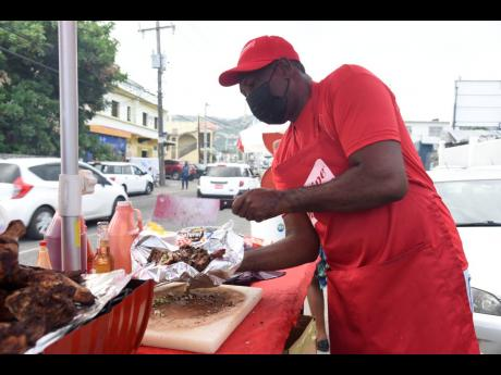 Jerk man Paul Walcott shows us how he flips the chopped chicken quarter from the board to the foil.