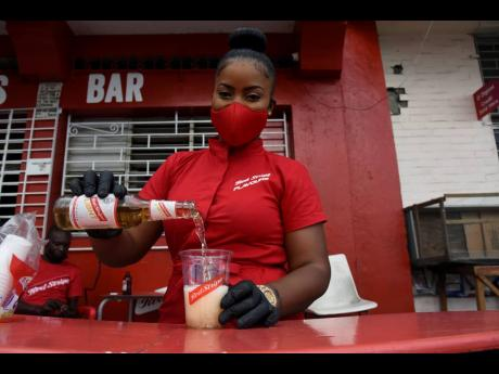 Red Stripe Brand Ambassador Sashanna Maxwell pours a cold cup of beer for customers to sip and enjoy.