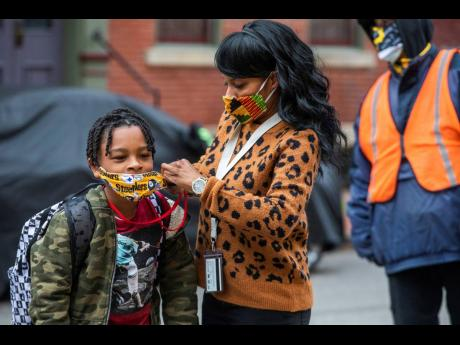 In this Monday, March 29, 2021, file photo, Jenea Edwards, of the North Side, helps her son Elijah, 9, in the third grade, with his mask before heading into Manchester Academic Charter School on the first day of in-person learning via a hybrid schedule, i