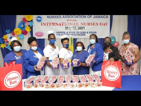 President of the Nurses Association of Jamaica, Patsy Edwards-Henry (third right), surrounded by senior nurses from select health centres across the island, display the delivery of Honey Bun donuts from the baking company's Donuts for Nurses initiative.