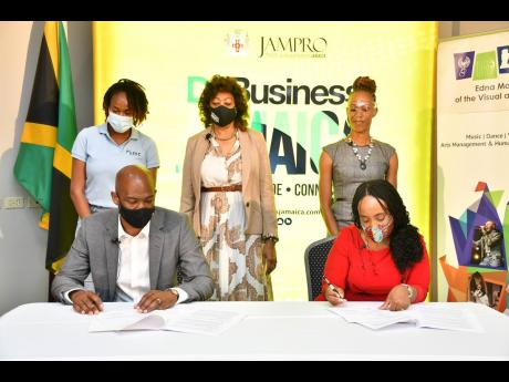 From left (seated): Maurice Hamilton, founder and CEO of the SMC Group and Dr Trudy-Ann Barrett, acting principal, Edna Manley College of the Visual and Performing Arts (EMCVPA), sign an agreement concretising their organisations' partnership to develop