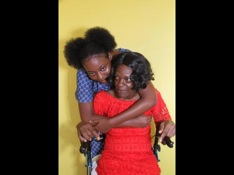 Spanish teacher Atonate Peters, who woke up one morning in 2019 to faded sight,which threw her life into a tailspin, gets a loving hug from her 17-year-old daughter Shoze Cammock.