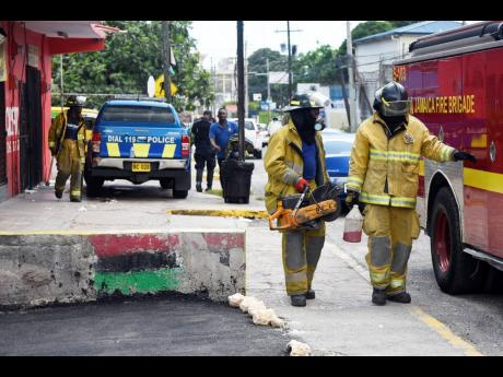 Firefighters prepare to leave the Travellers Rest Sports Bar on Old Hope Road, St Andrew, where Robert Fletcher was shot dead by gunmen on Monday. Fire and police crew returned on Tuesday to pry open a vault where two guns were recovered.