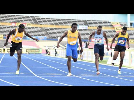 St Elizabeth Technical's Sachin Dennis (second left) wins the Class One Boys' 100 metres final in 10.53 seconds ahead of Antonio Watson (left) from Petersfield High, 10.58, at the ISSA/GraceKennedy Boys and Girls' Athletics Championships at the Natio