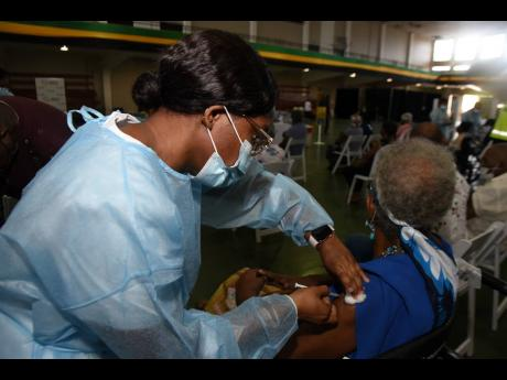 A senior citizen is inoculated with a dose of Oxford-AstraZeneca by a public health nurse during a vaccination blitz for persons 75 years and older at the National Arena on Saturday, March 27, 2021.