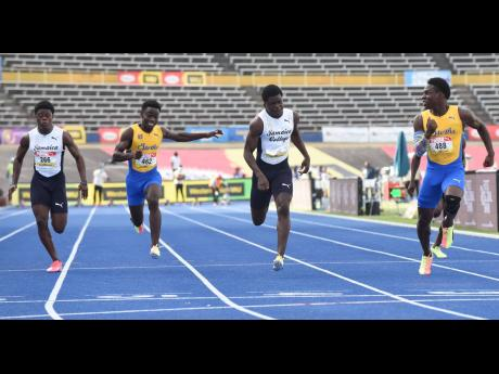 Orlando Wint, 10.79, (right) from St. Elizabeth Technical wins the Class Two boys 100 metres final ahead of Hector Benjamin, 10.74, (second left) from Jamaica College and Javorne Dunkley, 11.01, (left) from St. Elizabeth Technical at the ISSA/GraceKennedy