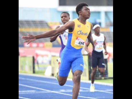 St Elizabeth Technical's Tramaine Todd celebrates after winning the Class Three boys 100m in 11.03 seconds at the ISSA/GraceKennedy Boys and Girls Athletics Championships at the National Stadium on Thursday.