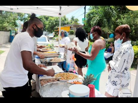 Young men in the community help to plate the delicious meals as the women, who were all dolled up for Mother's Day, collect their meals.