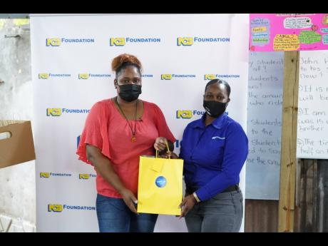 Zonya Pryce (right), NCB Foundation projects officer, gifts Melissa Powell with various items for her homework centre.