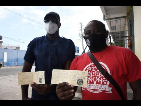 Correctional Officers Jovan Bedward (left) and Javier Bascoe display the COVID-19 vaccination cards, after receiving the two doses of the Astrazeneca vaccine.