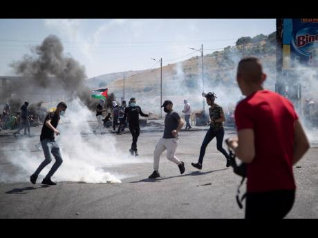 Palestinian protestors throw back a teargas canister during clashes with Israeli troops at the Hawara checkpoint, south of the West Bank city of Nablus, Friday, May 14.