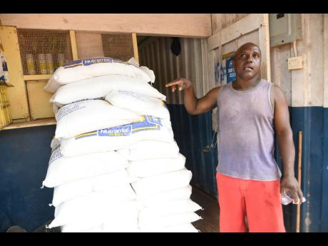 Ramunn Hanson explains some of the challenges facing him as a businessman. Here he is seen pointing to Nutramix feeds he sells from a container in Kitson Town.