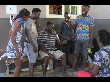 Mortel Pinnock (seated at centre) is surrounded by a group of young people at his business place in Wood Hall, Clarendon. Pinnock is the joint owner of a car wash and employs eight young people from the community.