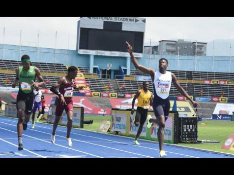 Jamaica College's Javain Brown (right) celebrates as he crosses the line for victory in the Class One Boys 400m final s ahead of Calabar High School's Jeremy Bembridge (left) and Holmwood Technical High School's Tahj Hamm (second left), who were second and
