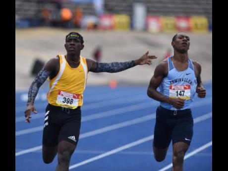Petersfield High School's Antonio Watson (left) gestures to Edwin Allen High School's Bryan Levell as he crosses the finish line ahead of him in the Class One Boys 200m final during the ISSA/GraceKennedy Boys and Girls' Athletics Championships at the Natio