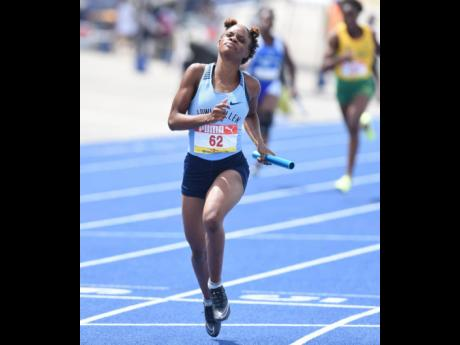 Edwin Allen High School's Tia Clayton crosses the line for victory in the Class Two Girls 4x100m final at the ISSA/GraceKennedy Boys and Girls' Athletics Championships at the National Stadium in Kingston on Saturday afternoon.