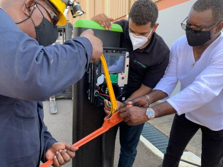 Wayne McKenzie, InterEnergy Country Manager, Jamaica, collaborates with Harold Frias, SCADA Engineer, InterEnergy Systems and Michael Hunt, Instrumentation & Electrical Technician, InterEnergy, to connect electrical wiring during a demo installation of an