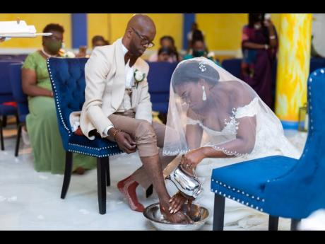 Andrea Edwards washes the feet of her husband, Markland, during their wedding ceremony.