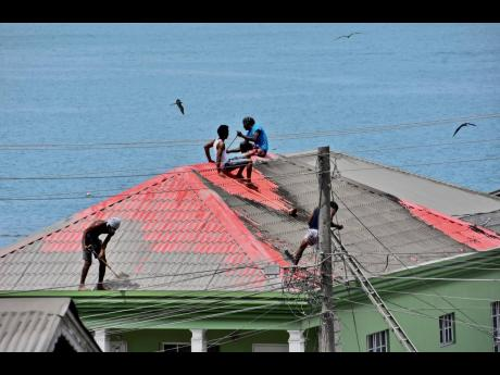 In this April 12, 2021 file photo, people clean volcanic ash from the red roof of a home after La Soufriere volcano erupted in Wallilabou on the western side of the Caribbean island of St Vincent.