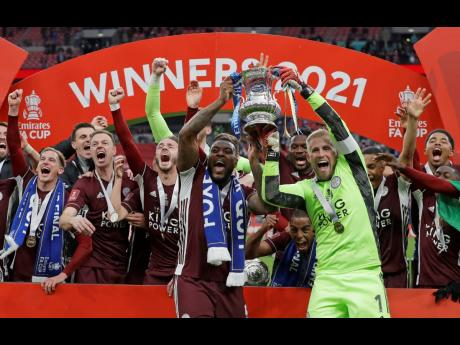 Leicester City goalkeeper Kasper Schmeichel (right) and Wes Morgan hold the trophy aloft at the end of the FA Cup final against Chelsea at Wembley Stadium in London, England, yesterday.