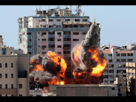 A ball of fire erupts from a building housing various international media, including The Associated Press, after an Israeli airstrike yesterday in Gaza City.