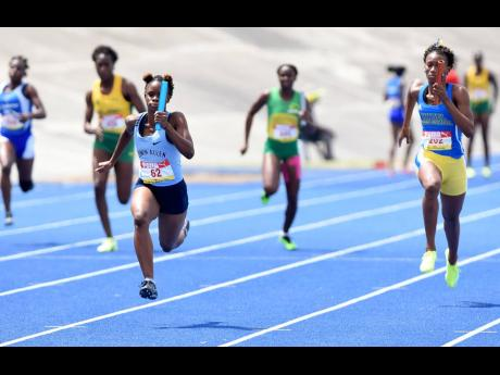 Tia Clayton (left) is in full flight as she anchors her Edwin Allen High School Class Two 4x100m relay team to victory during the ISSA/GraceKennedy Boys and Girls' Athletics Championships at the National Stadium yesterday.