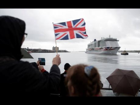 A person waves a Union Jack flag as the new P&O cruise ship 'Iona' arrives in Southampton, England, for the first time ahead of its naming ceremony on Sunday.