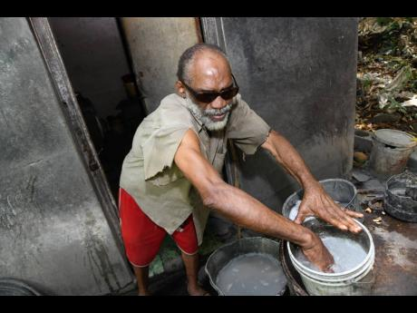 Beresford Dixon washes his hands in a bucket outside his house in Kintyre, St Andrew, on Thursday.