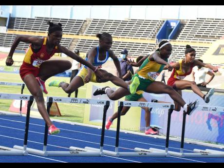 From left: Wolmer's Girls' School's Tiana Marshall clears the final hurdle in the Class Four girls' 70m hurdles final ahead of Hydel High School's Tihanna Reid, Vere Technical High School's Kecia King, and Wolmer's Natrilia Campbell at the IS