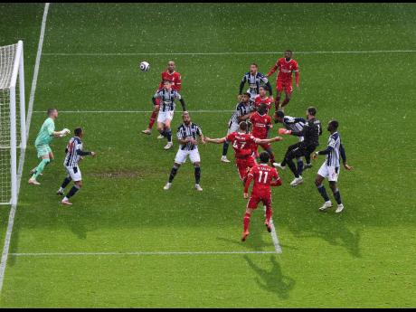 Liverpool goalkeeper Alisson (second right) scores his side's second goal during their English Premier League match against West Bromwich Albion at the Hawthorns Stadium in West Bromwich, England, yesterday.