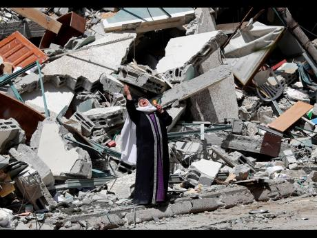 A woman reacts while standing on Sunday near the rubble of a building that housed The Associated Press, broadcaster Al-Jazeera, and other media outlets in Gaza City. The building was destroyed by an Israeli airstrike a day earlier.