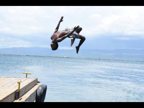 Prince Bryan, 18, leaps off the Port Royal Pier. Bryan, one of several teenagers who are members of JAPROS swimming club, could soon be one step closer to realising their Olympic dreams.