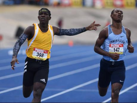 Petersfield High's Antonio Watson (left) celebrates with a gun play gesture towards Edwin Allen High's Bryan Levell as he crosses the finish line ahead of him in the Class One 200m final during the ISSA/GraceKennedy Boys and Girls' Athletic Champions