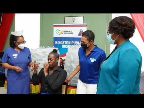 Kingston Public Hospital's (KPH) secretary Omoy Blake (second from left) demonstrates the use of a modified medical spacer, created by the Wisynco Group Ltd, as a gesture to assist respiratory patients battling COVID-19. The spacers were designed and cre